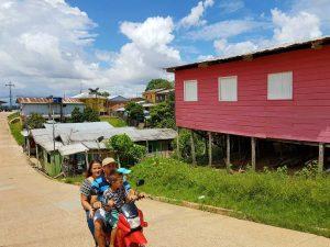 Dorf am Amazonas mit Motorradfahrern.