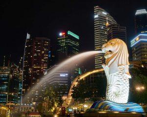 Der Merlion vor der Silhouette Singapurs bei Nacht